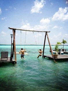 Swing set over shallow water.