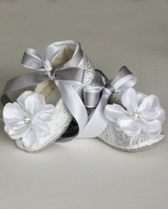 """For a fairytale wedding, a sparkly holiday occasion or, for those times when she just wants to feel like a princess, these silver and white brocade ballet slippers, with handmade satin magnolia blossoms on the toes, are just the ticket. Rhinestones """"diamonds"""" complete this vision of a shoe. The shoe can be worn with the white and silver double ribbon tied around the ankle, in a traditional ballet style, or it can be easily removed and the shoe worn as a flat. #timelesstreasure"""