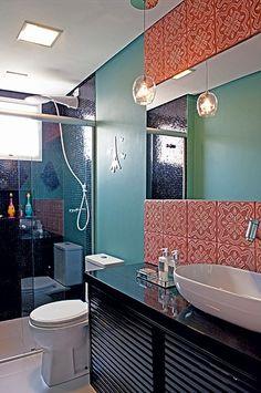 O banheiro tem placas de cerâmica artesanal. Já a parte molhada é mais sóbria, com pastilhas de vidro pretas. Projeto da designer de interiores Amanda Borges