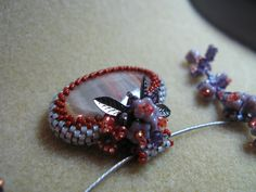 Beaded cabochon. I cut this cabochon and then beaded and embellished the bezel.  Earrings to match.  Made by Ellen