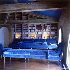 In Pauline de Rothschild's library at the Château Mouton Rothschild, blue velvet rules in perfect contrast with the brick walls and wooden beams. - HouseBeautiful.com