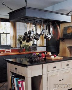 Remember to make storage and organization part of your aesthetic: Wood countertops and a rustic fireplace are warm complements to the deep hues of interior designer Malcolm James Kutner's London kitchen, where the heavy-duty pot rack by Chalon takes center stage.