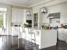 Designer Tamara Mellon's Hamptons kitchen is a sexy, neutral, 70s-meets-2010s affair, with silver pendant lights by Tom Dixon, custom-made cabinetry, and a Wolf oven and stove.   - ELLEDecor.com