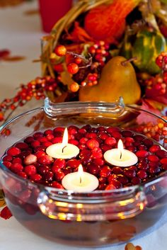 Floating candles in a bowl filled with water and red fruits = pretty centerpiece