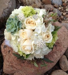 White roses, hydrangea, succulents, brooches, wedding bouquet in white and ivory.