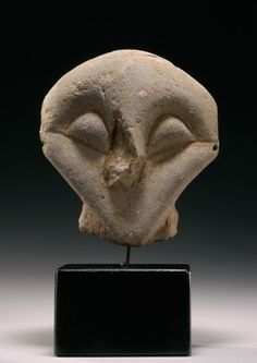 Neolithic pottery head from a larger piece. Roughly spade-shaped, with raised arching eyes surrounded by incisions, an incised cheek line, and a raised nasal ridge; the nose lacking; the back of the concave head with a row of four perforations.  Vinca Culture, ca. 5th Millennium BC