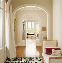 In the entrance hall, one is greeted by an elegant chaise longue and glass standing lamp.