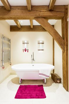 Contemporary roll-top bath in green oak frame house, by Roderick James Architects