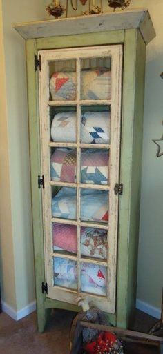 Add an old window pane door to a bookshelf for quaint quilt storage!