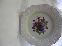 Stylish Nelson ware cake plate (similar size to a dinner plate) with beautiful florentine embossed border and gilt trim edge. a couple  of marks on the fruit design, otherwise in very good used condition. $15 +pp to Australia only.
