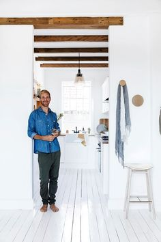 """Fräg used the original kitchen cupboard framework to create a new design. The timber beams are purely aesthetic, adding warmth to the white space. The floors are painted in Berger """"Jet Dry"""" paving paint."""