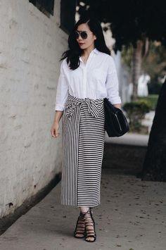 Hallie Daily in a striped maxi wrap skirt, white blouse, and strappy black heels