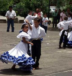 The young girl and boy are dancing to a local band in performing attire in Costa Rica.