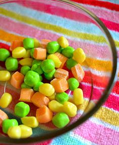 The carrots are quartered orange starburst.  The corn is yellow starburst cut into 6ths.  Then they get rounded a little and sculpted into corn kernel shapes.  The peas are rolled and rounded cuts of a laffy taffy.