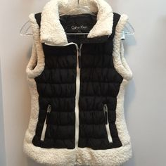"""Puffer Vest This vest is in great condition I wish it was my size. The puffy white might have been puffier when bough but I am selling for a friend so I don't know. Might look a little worn. Has two zip pockets and smartphone pocket . Body is 100% polyester lining is 100% nylon and fill is 100% polyester   Length is 22"""" down 15"""" across Calvin Klein Jackets & Coats"""