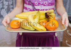 Bananas pears and tangerines on a metal tray. - stock photo
