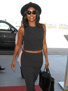 Gabrielle Union accessorized a knit skirt/crop top combo with a floppy fedora and demure cat-eye sunnies pre-flight!