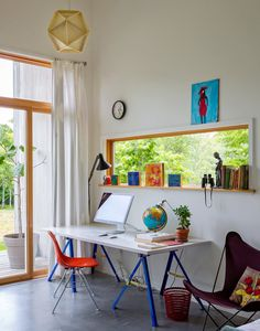 The Simple Modern Solution - Slide Show - NYTimes.com photo by Trevor Tondro  butterfly chair shell chair sawhorse legs desk large window folk art primary colors anglepoise lamp concrete floor modern glass doors clock pendant light origami
