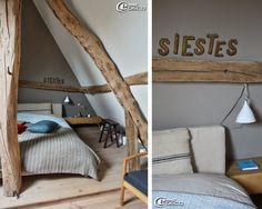 Dans la chambre aménagée dans les combles d'une longère, des coussins et plaid de la marque Caravane et une suspension Cornette en porcelain...