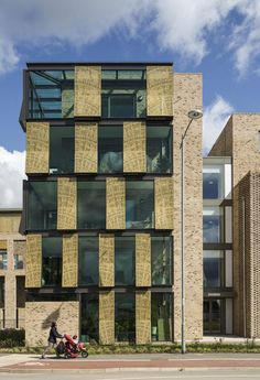 Perforated metal shutters in gold colour bring texture, colour and a contrast to the the building's glass and brick exterior. Cabinet D Architecture, Facade Architecture, Landscape Architecture, Tadao Ando, Cambridge United Kingdom, Cambridge England, Facade Design, House Design, Metal Shutters
