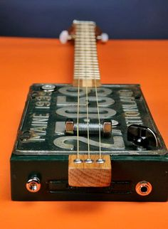 Vacationland 3-string Cigar Box License Plate resonator. Padron 3000 box (painted green); 1939 Maine license plate; oak neck with walnut & oak peg head; walnut/maple skunk-stripe fret board with inlaid walnut and maple dots. Piezo disc attached to neck under bridge. 24-inch fret scale.
