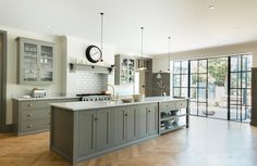 How gorgeous is this painted kitchen by deVOL! The grey/sage green tones are so calming and the extra-large island is ideal for those who love entertaining.