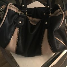 Steve Madden doctor's bag/purse Chic, roomy black & cream purse (pre-owned) with handles & detachable shoulder strap. Zipper details on one side & working zipper. Black & cream chevron stripe lining with zippered pocket, ph pocket & access pocket. The bottom of the zippered pocket has a grease stain but it's not visible. The lining is otherwise clean with the exception of one tiny mark. Some cracks & peeling on the handles & shoulder strap but not too noticeable. I'm not positive of the material, no tag but looks like leather. Steve Madden Bags Satchels