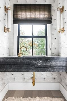 Black and white graphic print wallpaper covers the wall of this gorgeous black and gold bathroom lit by Studio VC Openwork Long Sconces fixed on facing walls.