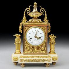 """Pendule dit de mariage en marbre blanc et bronze ciselé et doré d'époque Louis XVI surmontée d'une vasque et à décor de deux colonnes surmontées des oiseaux sur un coté et flambeau sur l'autre.Riche ornementation de bronzes ciselés et dorés.Le cadran signé """"MERRA à Paris"""" - Pierre l'aîné Merra, horloger reçu maître en 1772Mouvement à fil d'origine d'époque Louis XVI - révisé et en parfait état"""