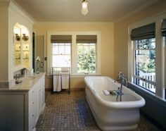 "Treat the tub like furniture. ""The owner just fell in love with this tub and had to have it,"" says Colleen Knowles of knowles ps. ""It worked perfectly in this older home, where we transformed an extra bedroom into a fabulous master bathroom. The vanities and tub look like furniture items set around the room in an interesting way, and the layout leaves the large, original windows unobstructed."""