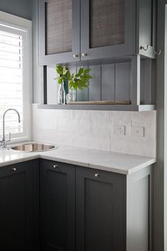 Stunning white and gray butler's pantry boasts dark gray shaker cabinets fitted small polished nickel knobs fixed beneath an l-shaped white quartz countertop finished with a round overmount stainless steel sink paired with a polished nickel gooseneck faucet fixed in front of a window dressed in white blinds.