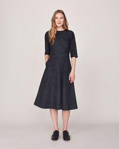 Flared, full and swingy skirt dress, with a fitted body, in real-indigo dyed, washed cotton cotton denim. Wide, boat-ish neck. Elbow length sleeves. Two carpenter pockets. Belt loops in waistband. Exposed metal zip and puller at back.