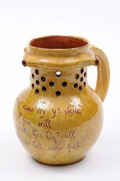 An Edwin Beer Fishley (Fremington) pottery jug of bulbous form with raised pieced neck the rim with three spouts the hollow handle with a pair of scroll terminals incised 'Here, Gentlemen, come try yr skill, See hold a wager if you will, That you don't drink this liq'r all, Without you spill or let some fall