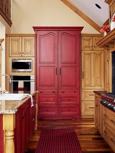 BHG.  Going with a bold colour throughout an entire space may be asking a bit much in terms of commitment.  By concentrating colourful cabinetry in the right places may do the trick.  Here the island and armoire style pantry compliment each other and the look is pulled together with the black and red checked runner.