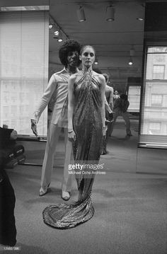 Sly Stone of the psychedelic soul group 'Sly And The Family Stone' in fashion designer Halston's studio standing behind a model wearing his future wife's gold wedding dress on June 19, 1974 in New York City, New York.