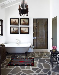 """Bathroom. The bathroom floor is made of Ojai river rock. """"It's so strong, you could build a Hyatt Regency on it,"""" McDowell says. She designed the shower door in the style of a metal casement window. Shower faucet by Sunrise Specialty. Cast-iron tub from the Tub Connection."""