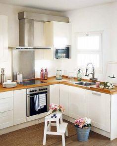 Cocina con encimera de madera y muebles blancos