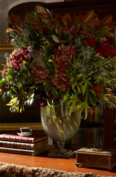 A teeming floral arrangement from Ralph Lauren Home beautifully combines magnolia leaves, oilve branches, hydrangea, lilac, clemeatius and thistle