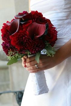 A BEAUTIFUl bridal bouquet of red dahlias and mini-calla lilies with a touch of seeded eucalyptus around the bottom. A stunning arrangement which is affordable and made with flowers that are available year-round from GrowersBox.com.