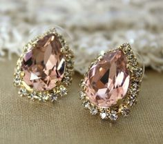 Rain drop shaped, light pink stone, diamonds around it. On my ears. Put them there, now!