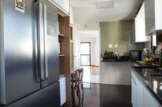 Na cozinha aproveitamos os armários e os adaptamos para os novos equipamentos usando um MDF madeirado para dar cor e aconchego no ambiente. O piso trocamos para um preto, na mesma cor da nova bancada. Nas paredes mantivemos os azulejos brancos e fizemos detalhes com patilha em tom de verde, dando charme e vida.