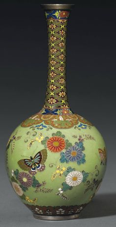 A Cloisonné Vase  Signed on a silver tablet Namikawa Yasuyuki, Meiji Period (late 19th century) Worked in silver wire and various coloured cloisonné enamels with butterflies among chrysanthemums and scrolling foliage on a pale green ground, the shoulder with foliate lappets containing paulownia interspersed with stylised chrysanthemums, the tall tapering neck with shippo-hanabishi, silver rims