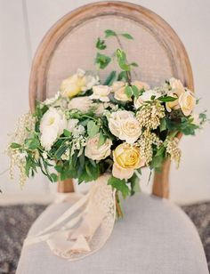 A lush arrangement features a variety of cream-colored garden roses combined with greenery and pieris japonica | Brides.com