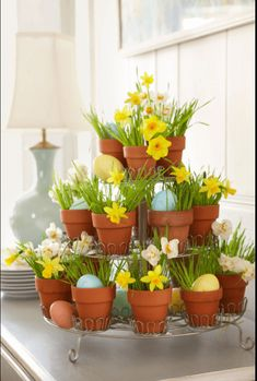 Tiered Daffodils - This tiered centerpiece is made bright and beautiful with faux mini daffodils. To DIY: You can enlist the help of a tiered cupcake holder by using small terra cotta pots. Stuff with faux grass sprigs, mini daffodils and small Easter eggs.