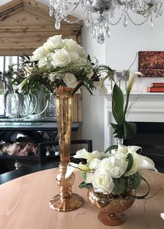 white calla, mini calla, roses, hydrangea cushion poms, copper curly willow, Lilly grass, and ruscus tie it all together in murky glass high and low centerpieces