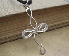 We designed,hammered and twisted 18 gauge sterling silver wire to make this Celtic knot influenced loopy cross pendant. The pendant measures