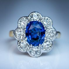 Antique French Sapphire Diamond Engagement Ring, Circa 1910. A platinum topped 18K gold ring of a classic cluster design is centered with a 2.34 ct cushion cut natural sapphire of a superb medium blue color surrounded by eight sparkling old mine cut diamonds, ~ 2.30 ct.