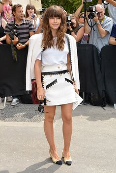 She makes the tweed skirt suit look chic, not stuffy, by styling it with a classic white T-shirt rather than a silk blouse. Skirt, jacket, shoes, and bag, Chanel