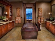 A beautiful deep brown soaking tub is the star of this traditional bathroom, which also features a pair of matching vanities, tile flooring and neutral curtains that frame the tub.