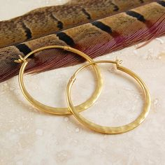These Small Hammered Gold Hoop Earrings are a timeless classic with a twist. Gorgeous hoops are slightly flattened in a graduated fashion toward their base. In this range: Large Hammered Gold Hoop Earrings These Small Hammered Gold Hoop Earrings are also available in sterling silver and rose gold. #Otisjaxon #Jewellery